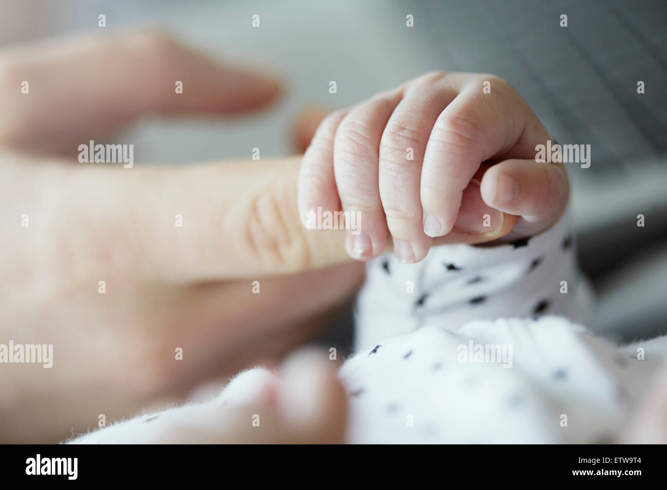 Close-up of baby holding father's finger - Stock Image