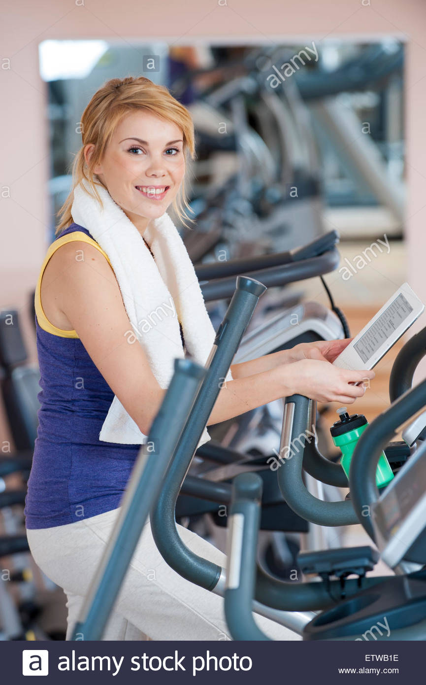 Portrait of smiling young woman with e-book in a gym - Stock Image