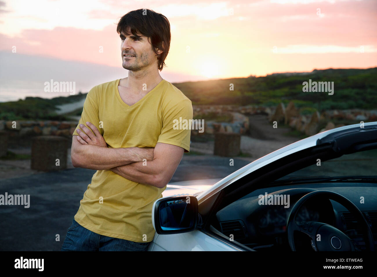 South Africa, smiling man at parked car at sunrise - Stock Image