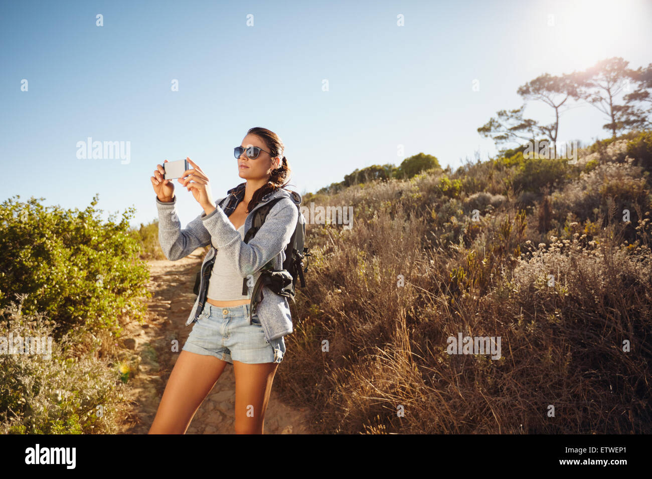 Image of young woman talking photographs with her mobile phone while hiking. Caucasian female trekking on a summer - Stock Image