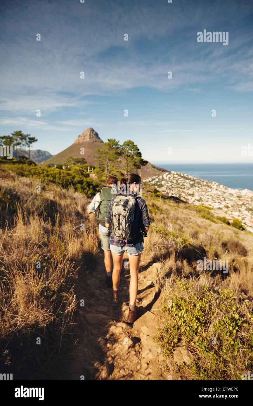 Rear view of couple walking through country path on mountain. Young man and woman hiker hiking in nature. Trekking - Stock Image