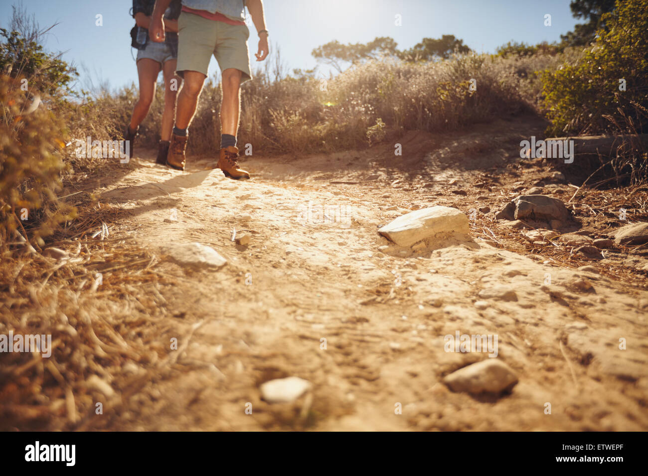 Low angle view of two people hiking along a dirt trail in the wilderness.  Couple of hikers walking on country path. - Stock Image