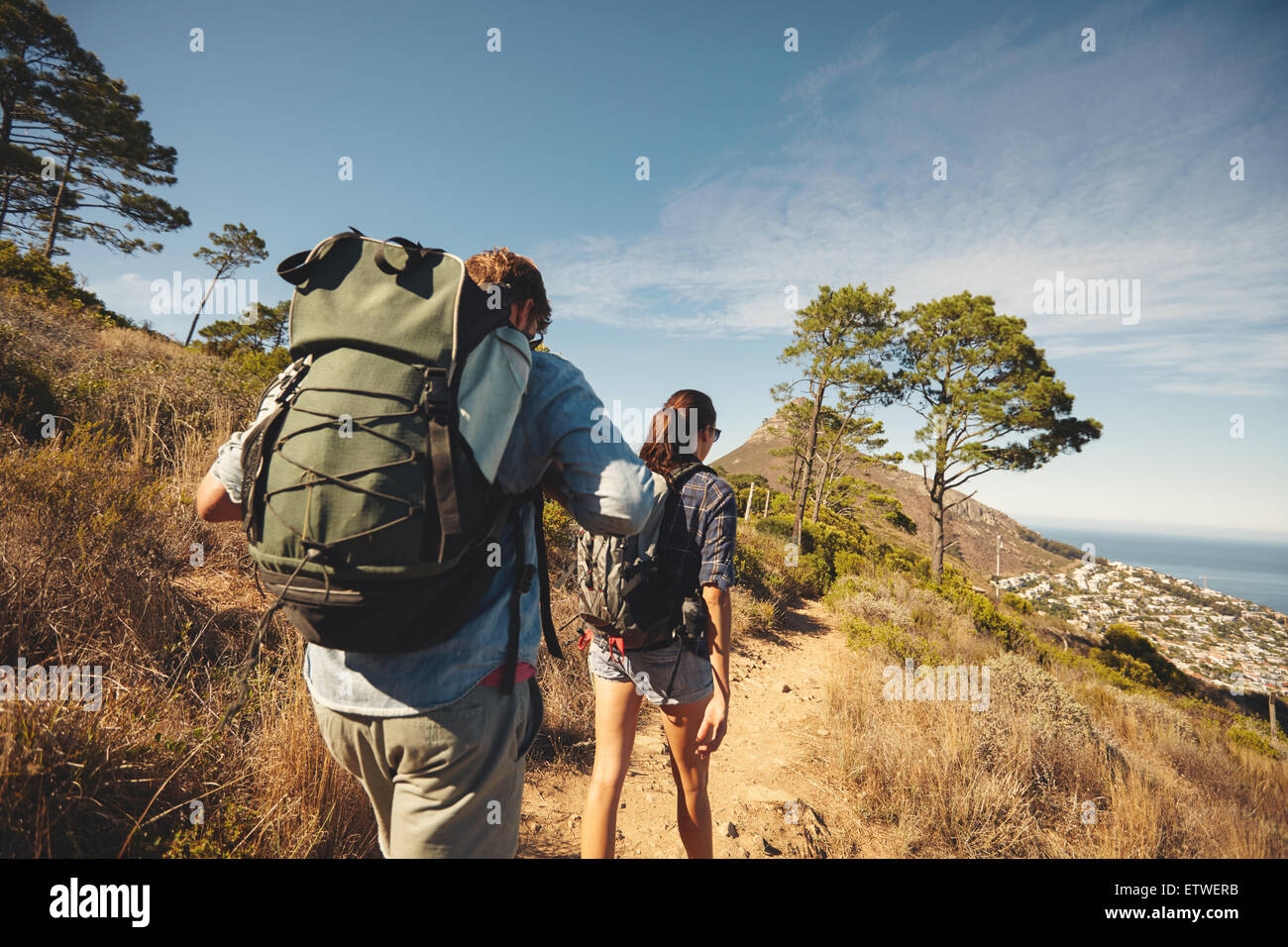 Rear view of two young people walking down the trail path on mountain. Young couple hiking with backpacks. - Stock Image