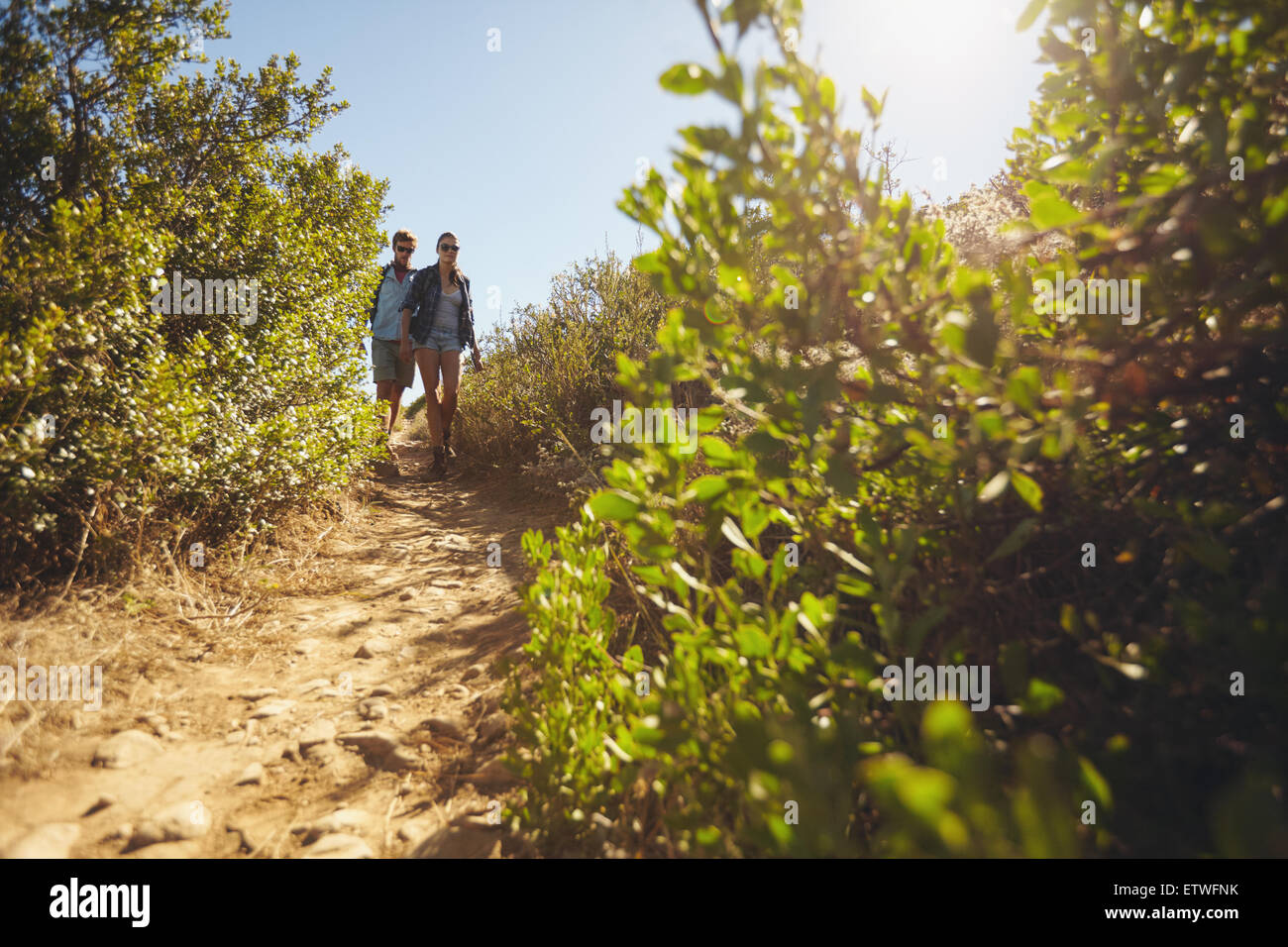 Image of two young people walking downhill. Young couple hiking on mountain on a summer day. - Stock Image