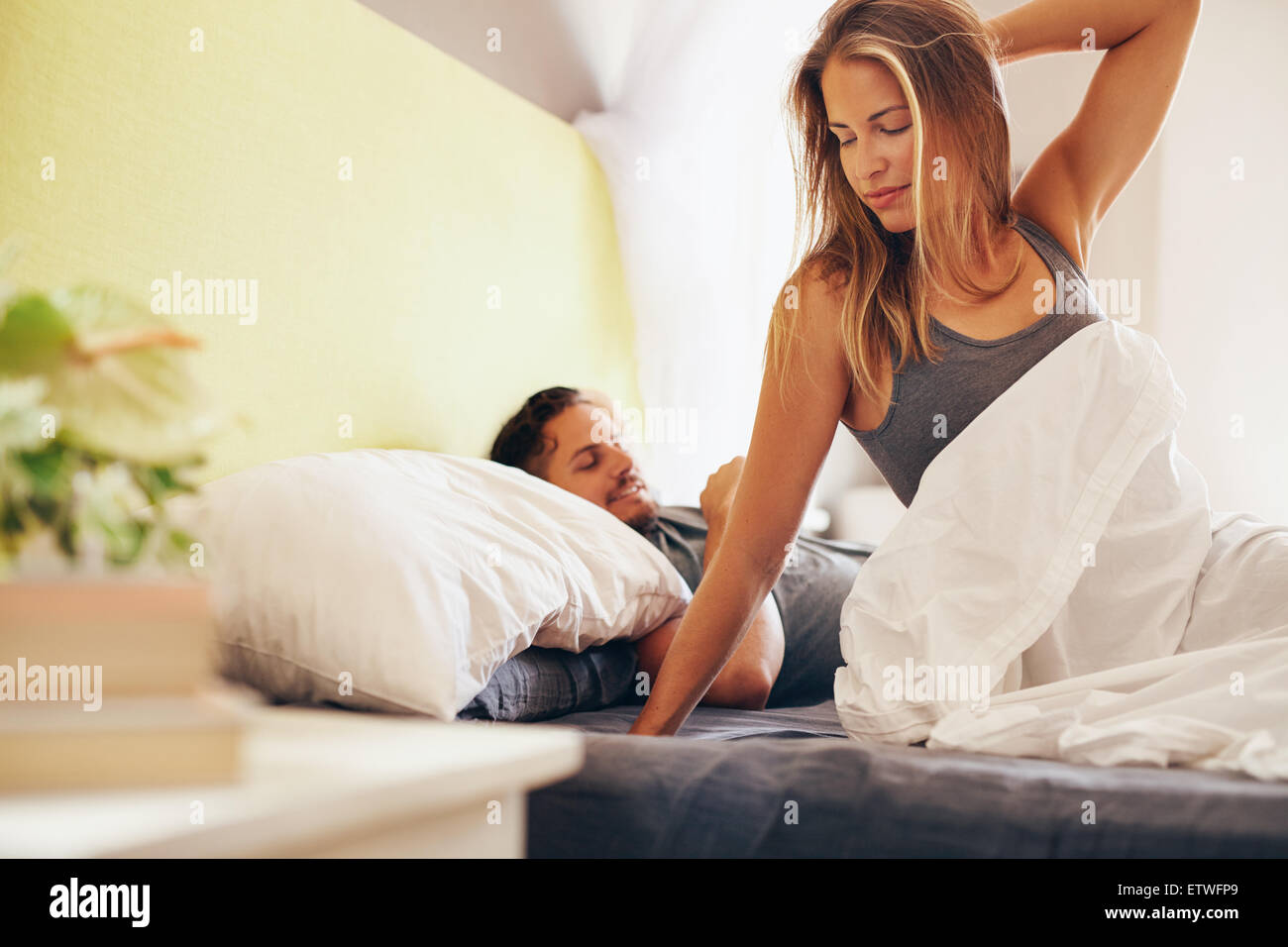Portrait of beautiful young woman waking up in morning with her husband sleeping peacefully behind her - Stock Image