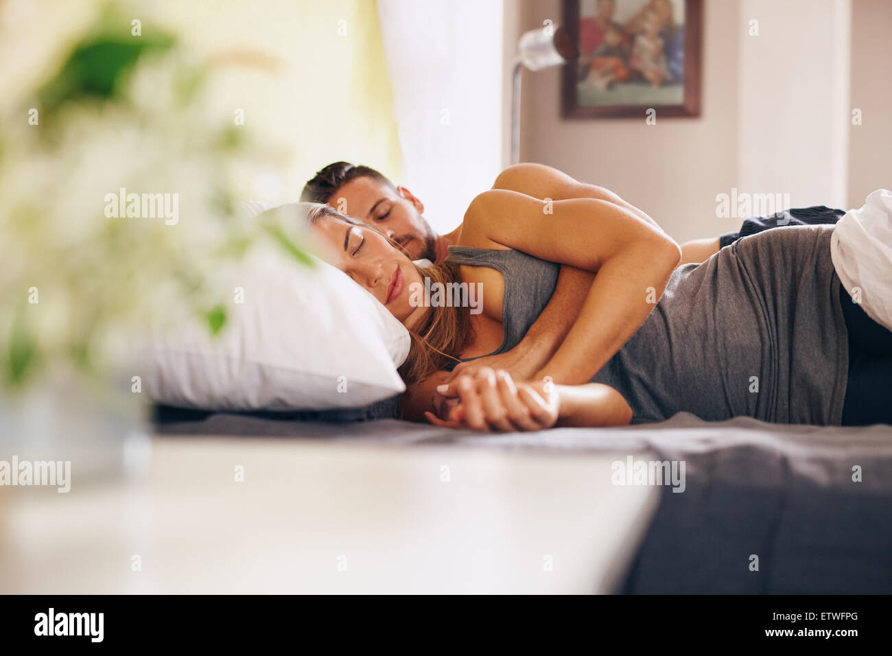 Image of young couple sleeping soundly in bed together. Husband and wife sleeping together in their bedroom. - Stock Image