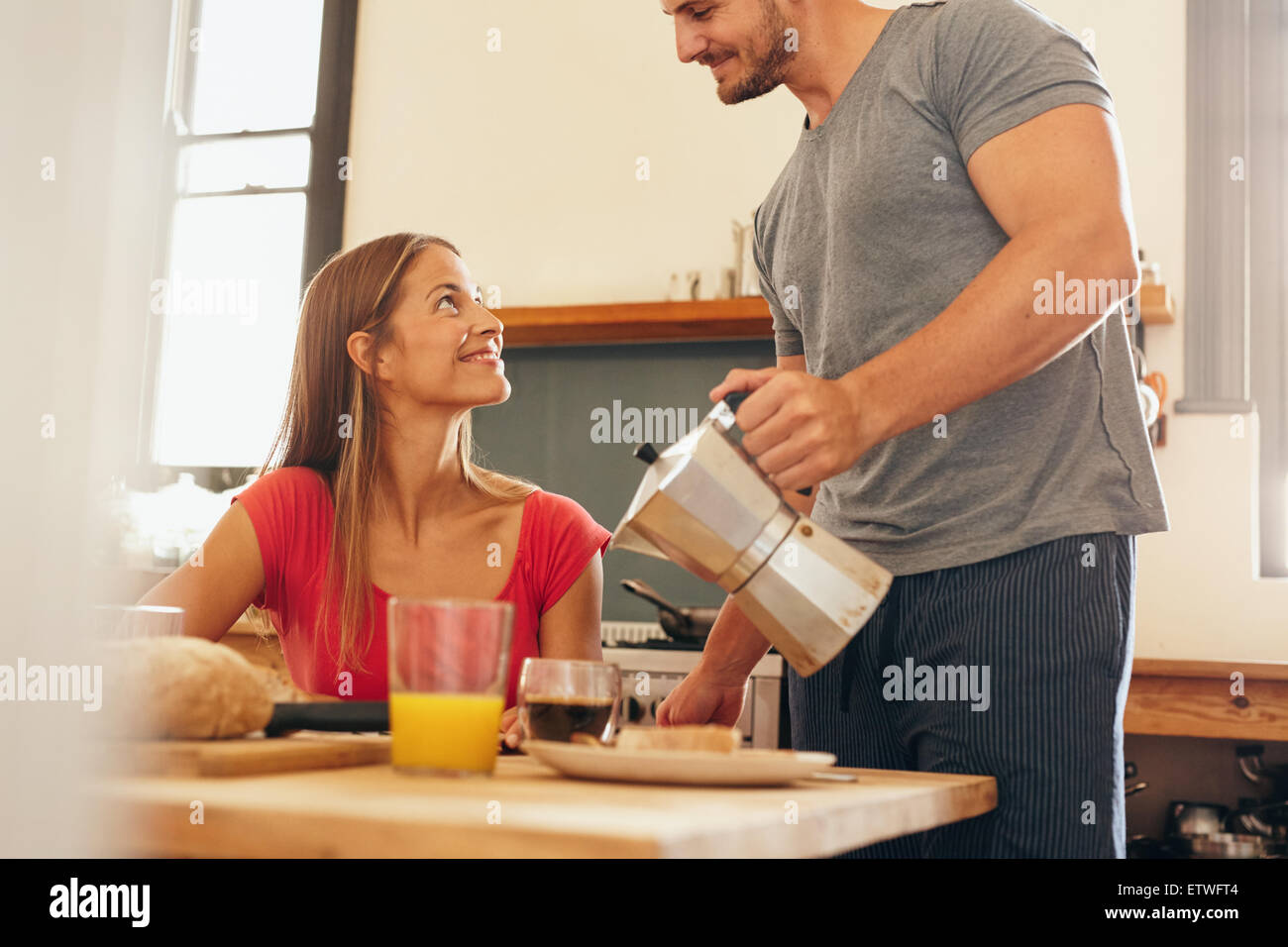Shot of young couple having breakfast in kitchen. Young man standing and serving coffee with woman sitting by breakfast - Stock Image