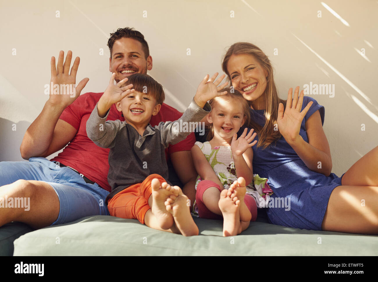 Family sitting on couch smiling and laughing together, waving at camera. Couple with kids on patio having fun outdoors - Stock Image