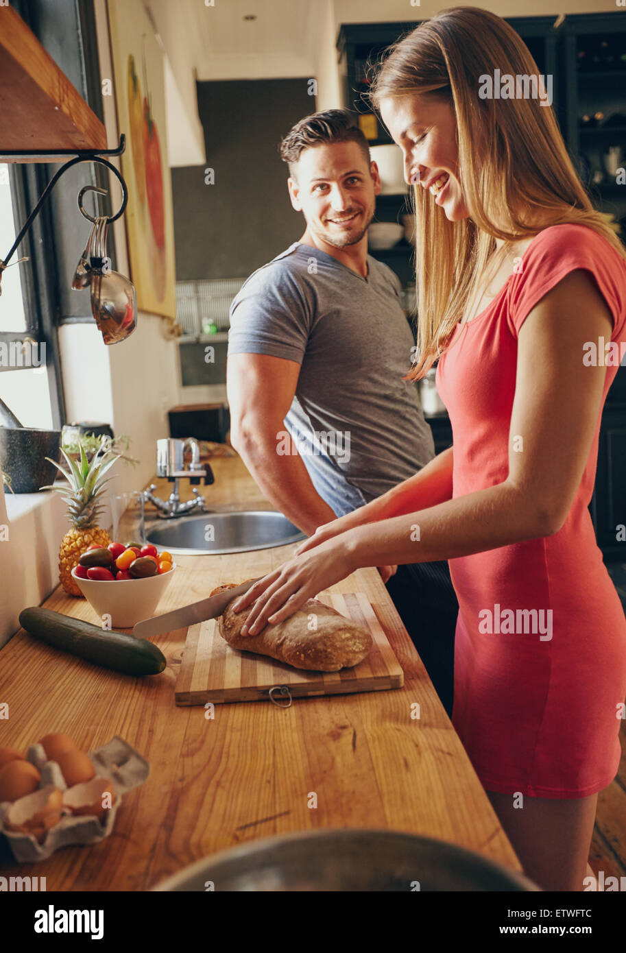 Caucasian couple together in the kitchen in morning. Focus on young woman cutting bread, while her husband standing - Stock Image