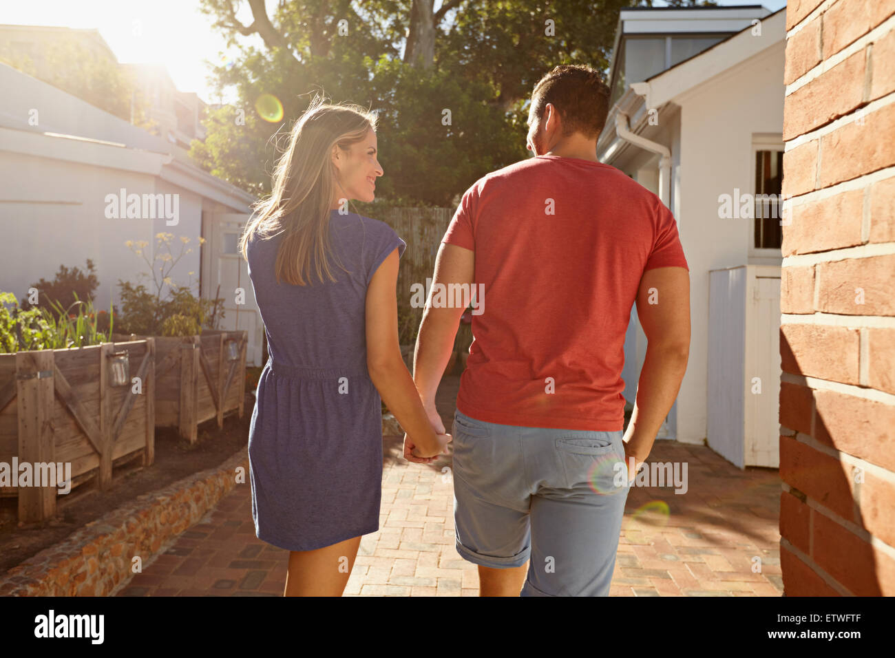 Rear view shot of a young couple taking a walk holding hand in hand outside in their backyard. Loving young couple - Stock Image