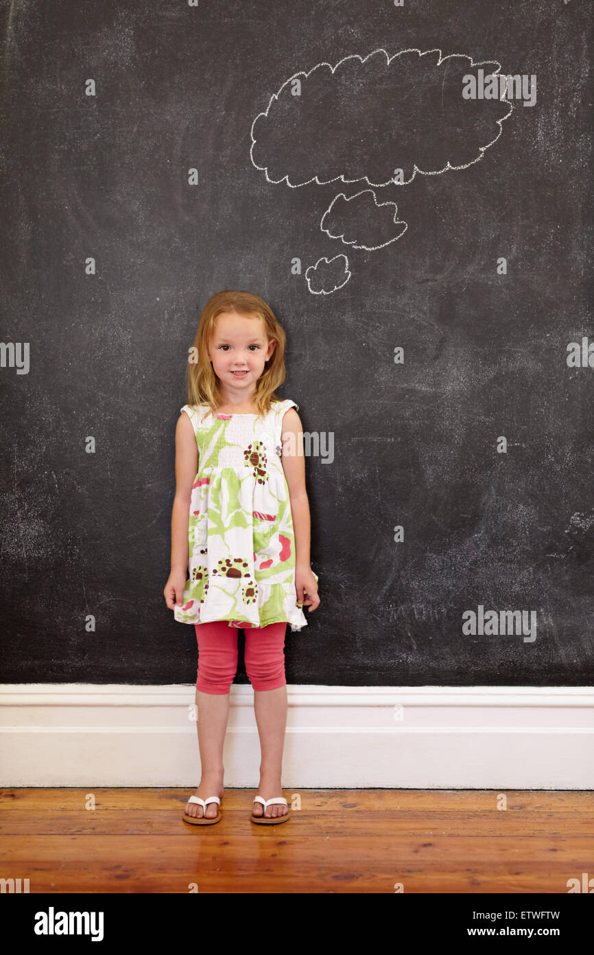 Sweet little schoolgirl with a thought bubble on blackboard looking at camera. Full length shot of caucasian young - Stock Image