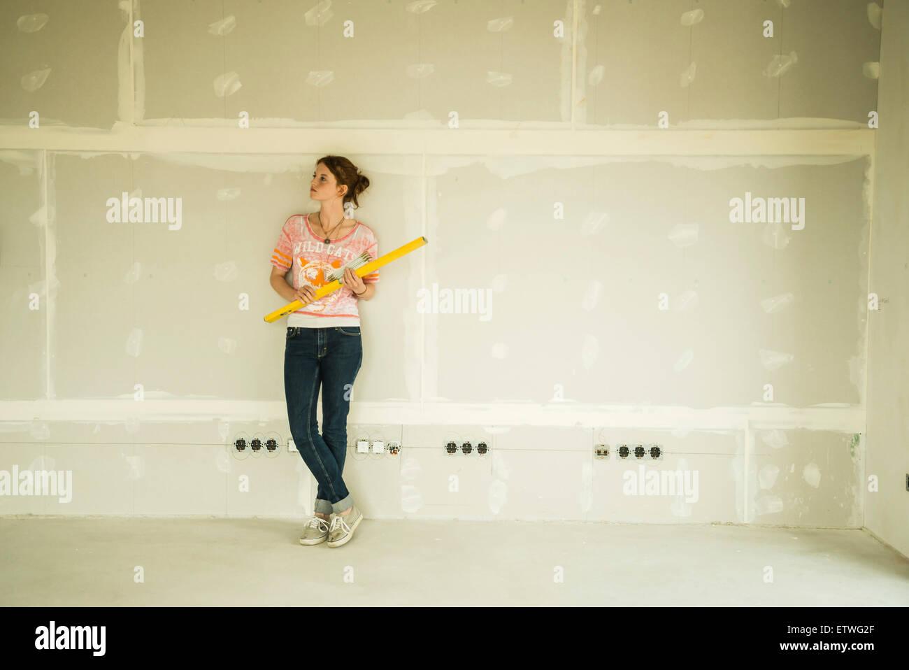 Young woman renovating standing at blank wall - Stock Image