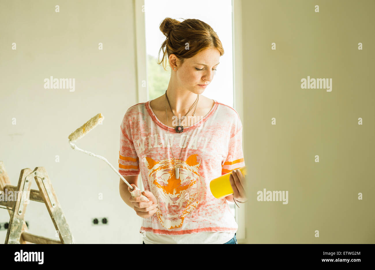 Young woman holding paint roller - Stock Image