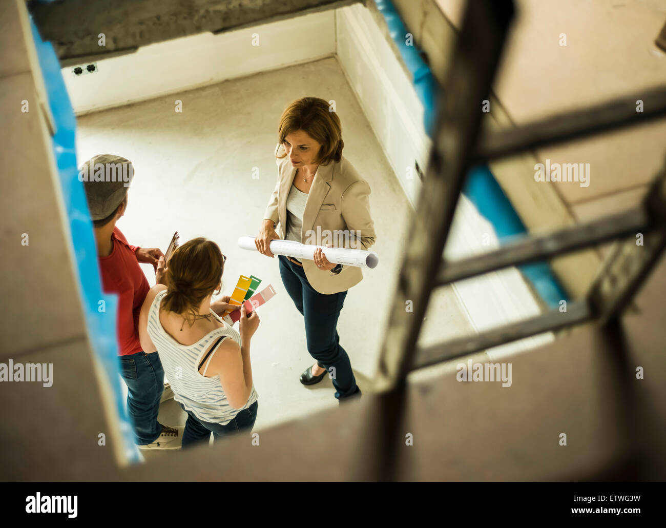 Architect and young couple discussing colour sample and construction plan - Stock Image