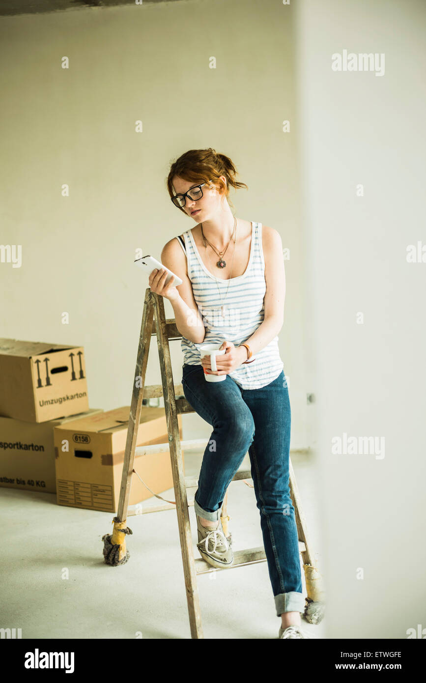 Young woman having a break form renovating - Stock Image