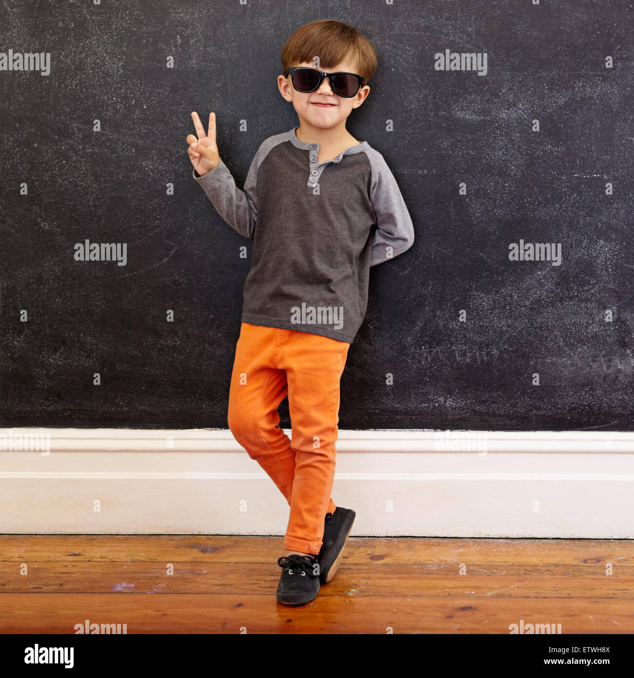 Full length shot of cool little boy wearing sunglasses gesturing victory sign. Young school boy in casuals showing - Stock Image