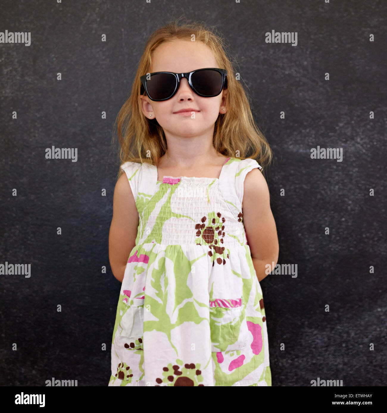 Portrait of beautiful little girl wearing sunglasses posing at camera against a black wall. Stock Photo