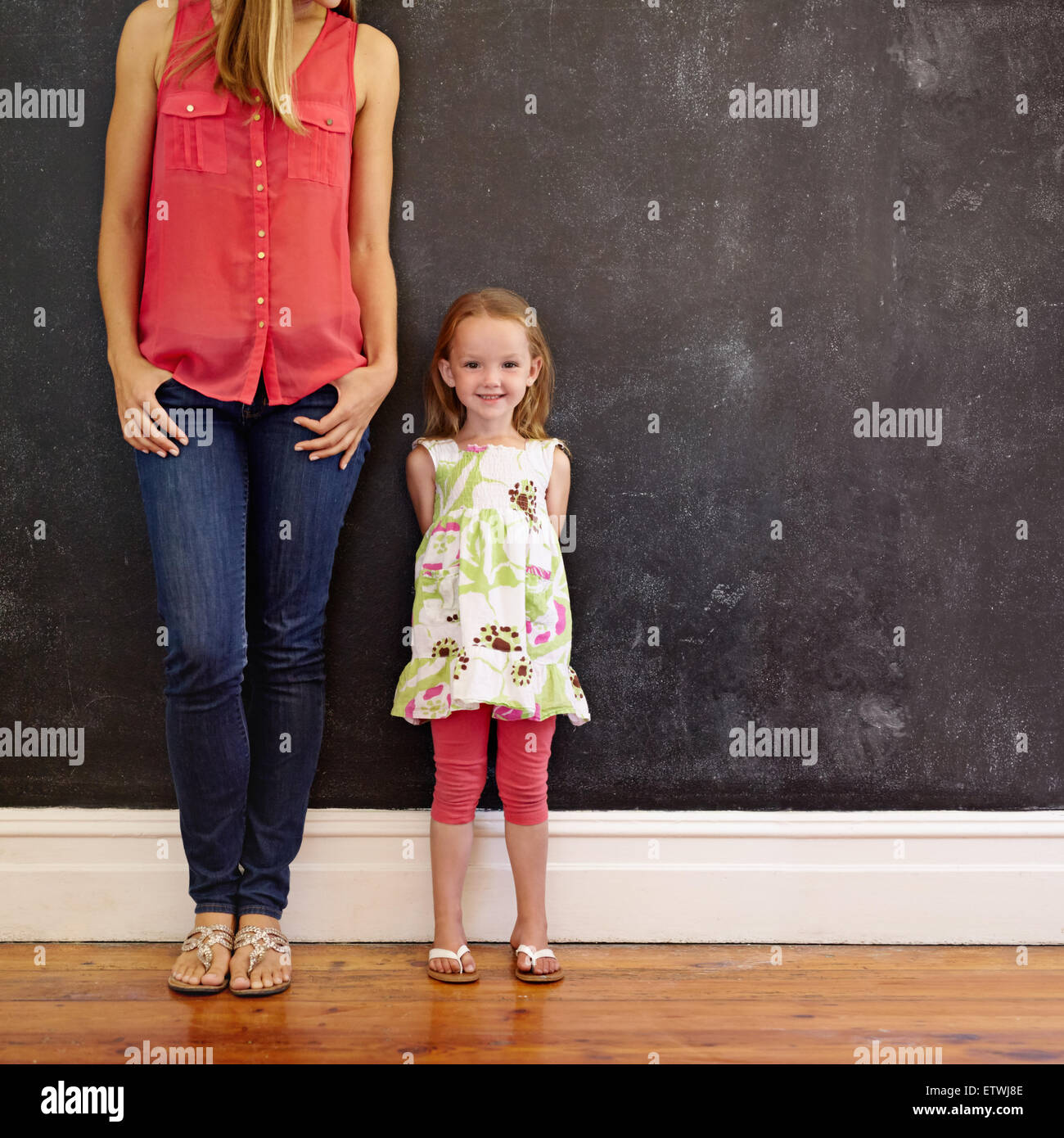 Indoor shot of beautiful little girl standing with her mother smiling. Mother and daughter posing against a black - Stock Image