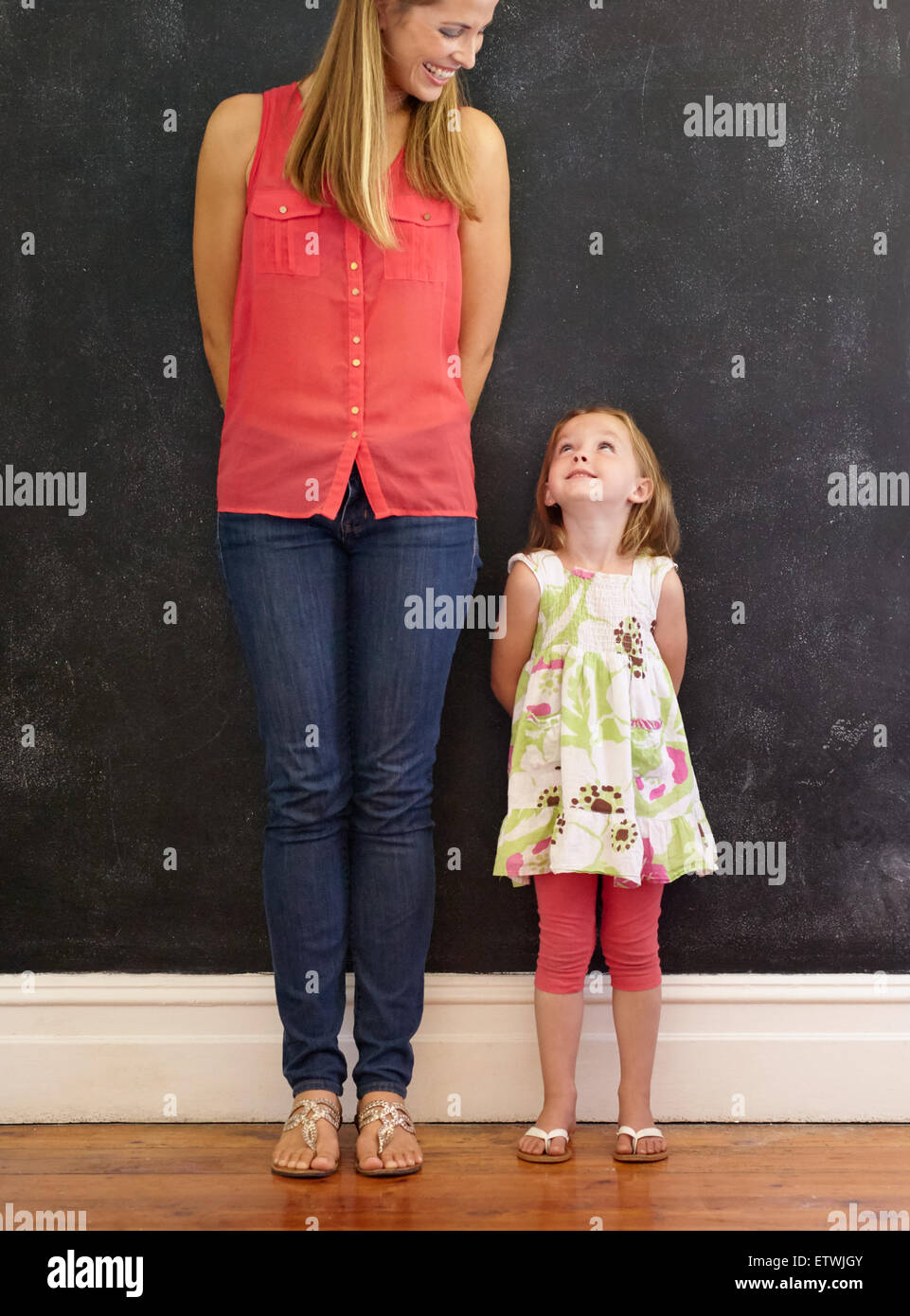 Indoor shot of little girl standing with her mother at home. Mother and daughter looking at each other smiling. - Stock Image