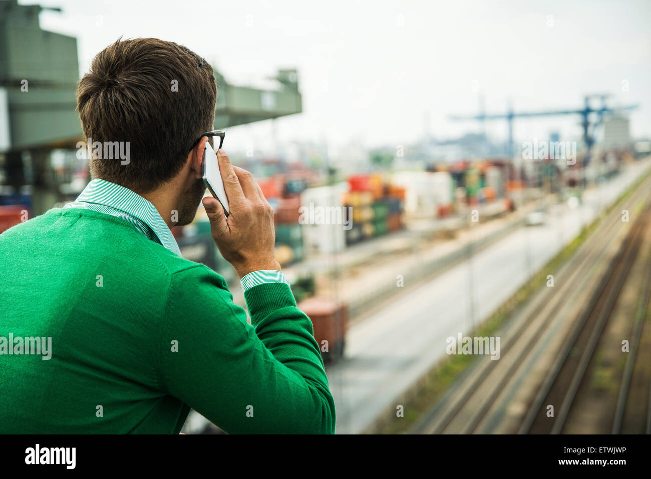 Man at freight yard talking on cell phone - Stock Image