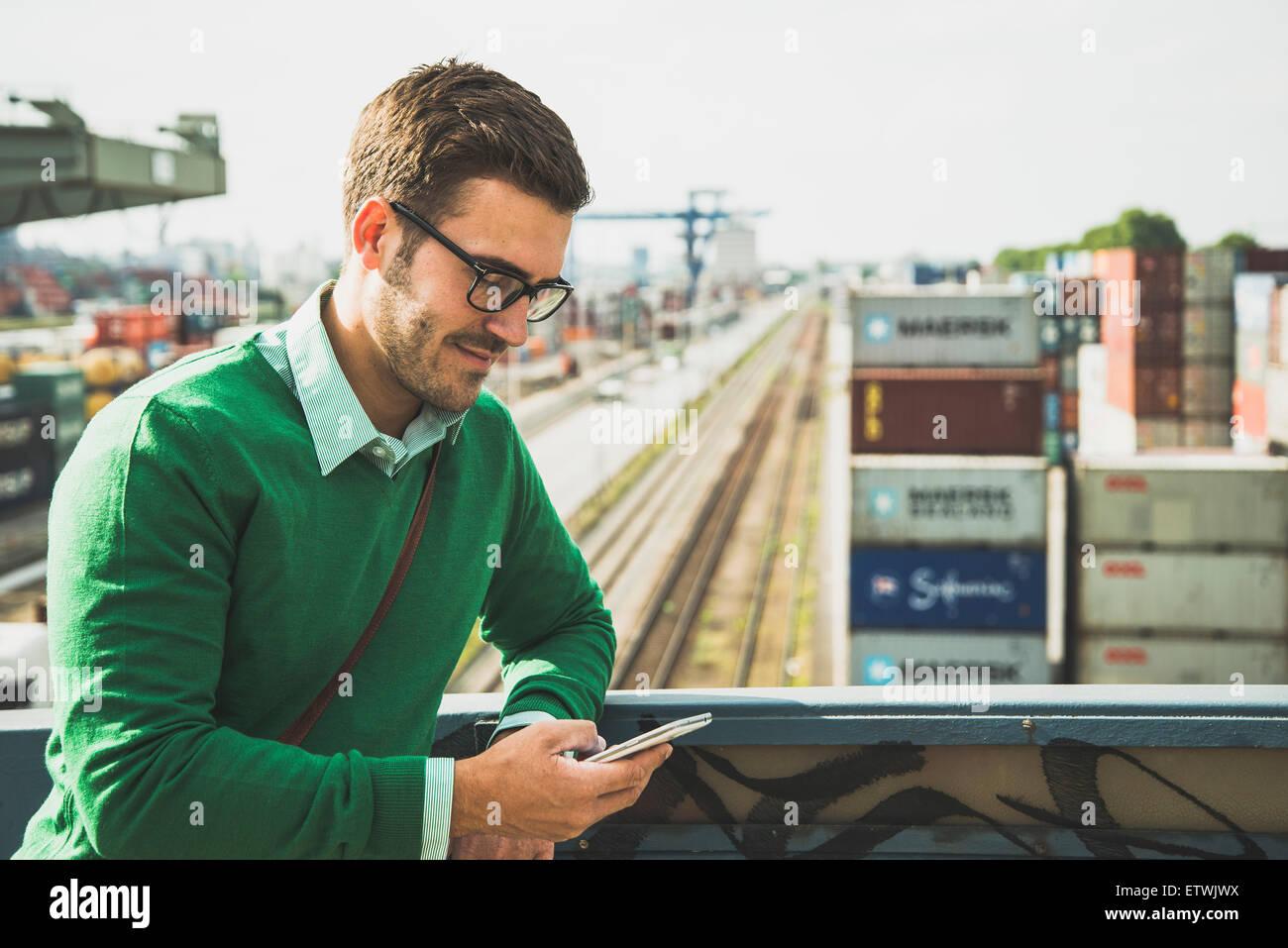 Man at freight yard looking at cell phone - Stock Image