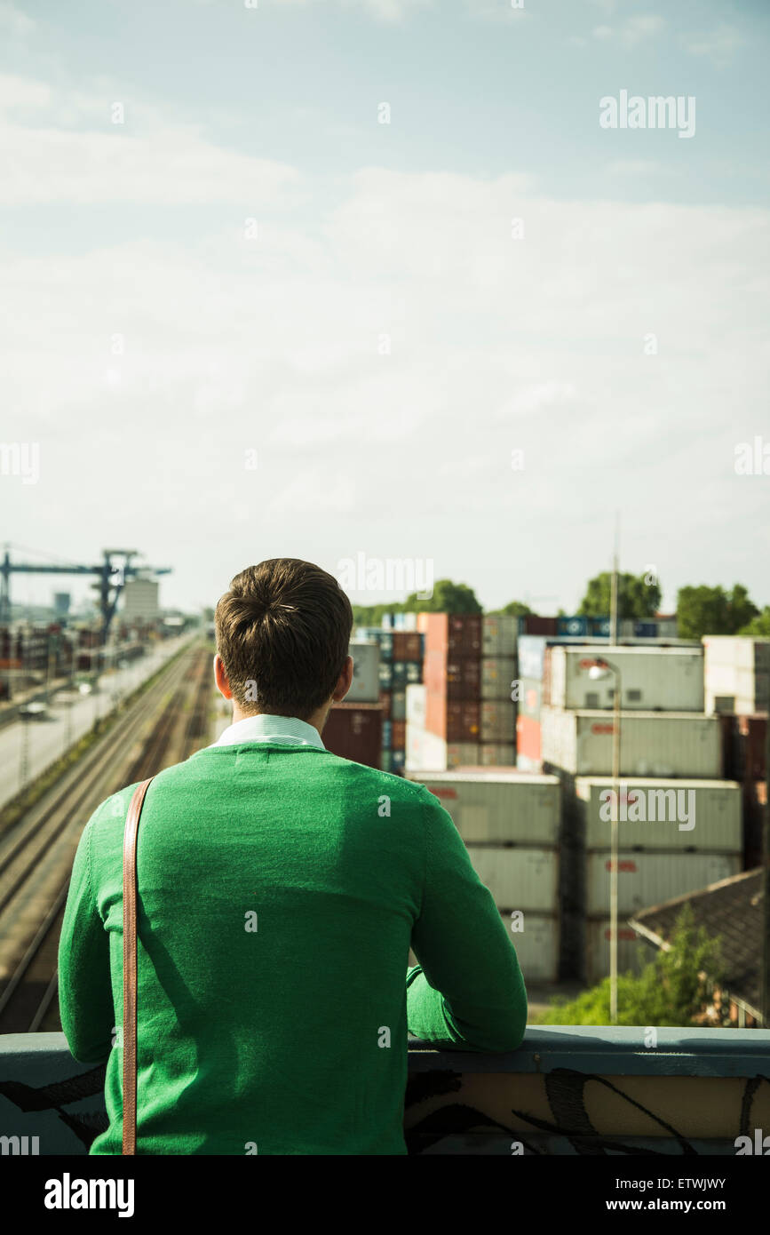 Man outdoors looking at freight yard - Stock Image