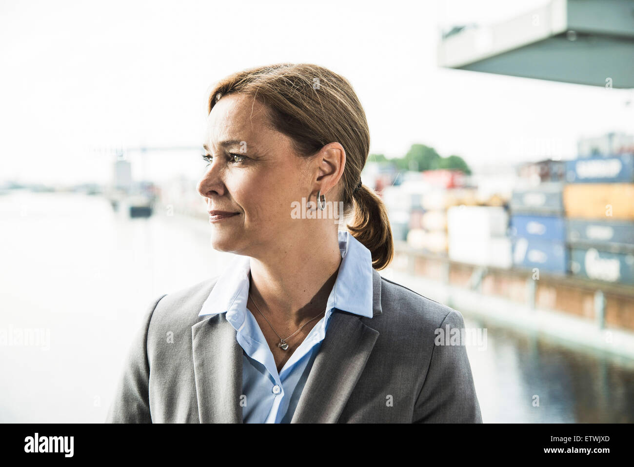Businesswoman at container harbor looking sideways - Stock Image