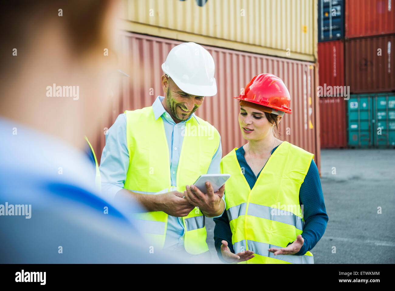 Woman and smiling man with safety helmets and digital tablet at container port - Stock Image