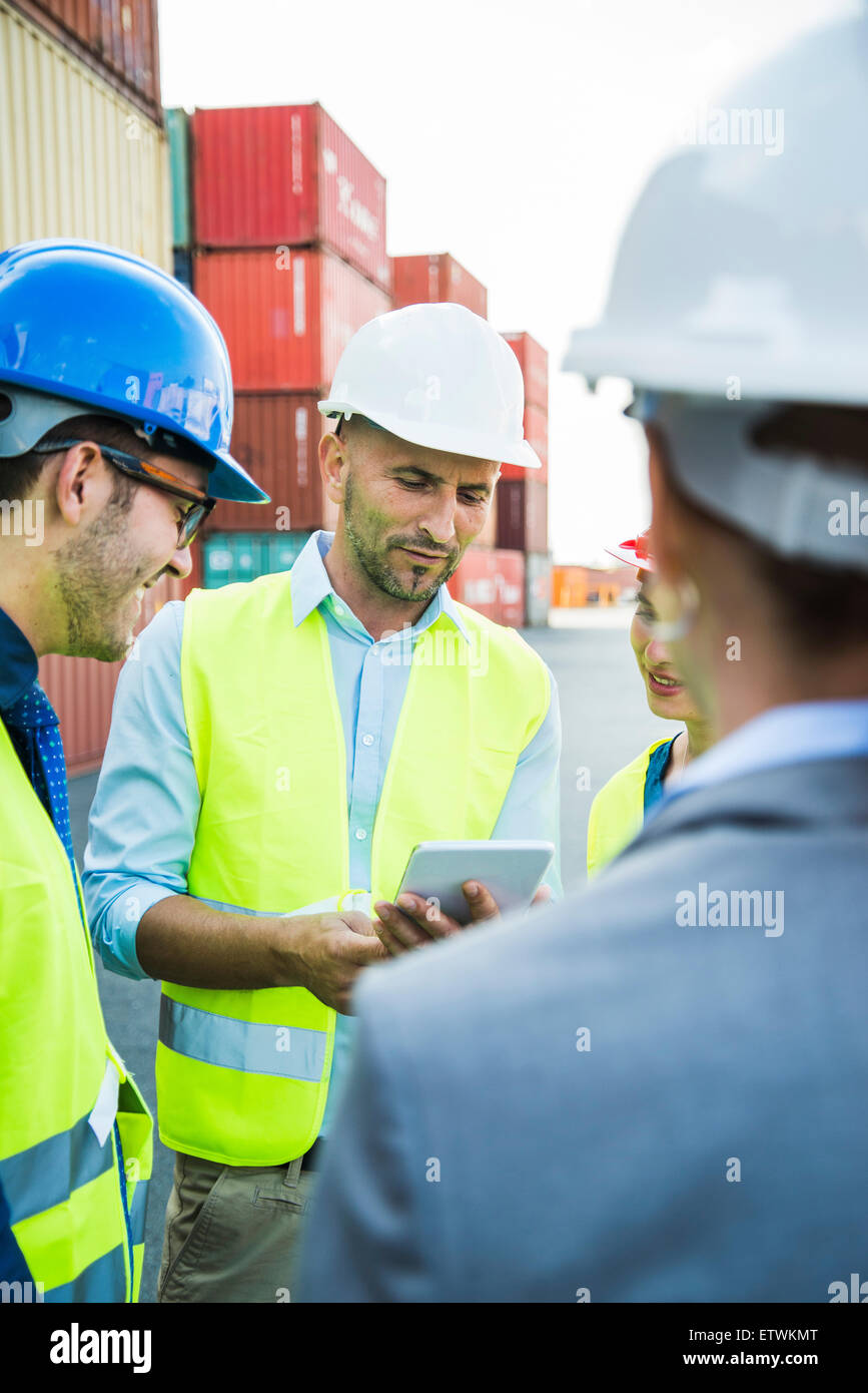 Four people with safety helmets and digital tablet talking at container port - Stock Image