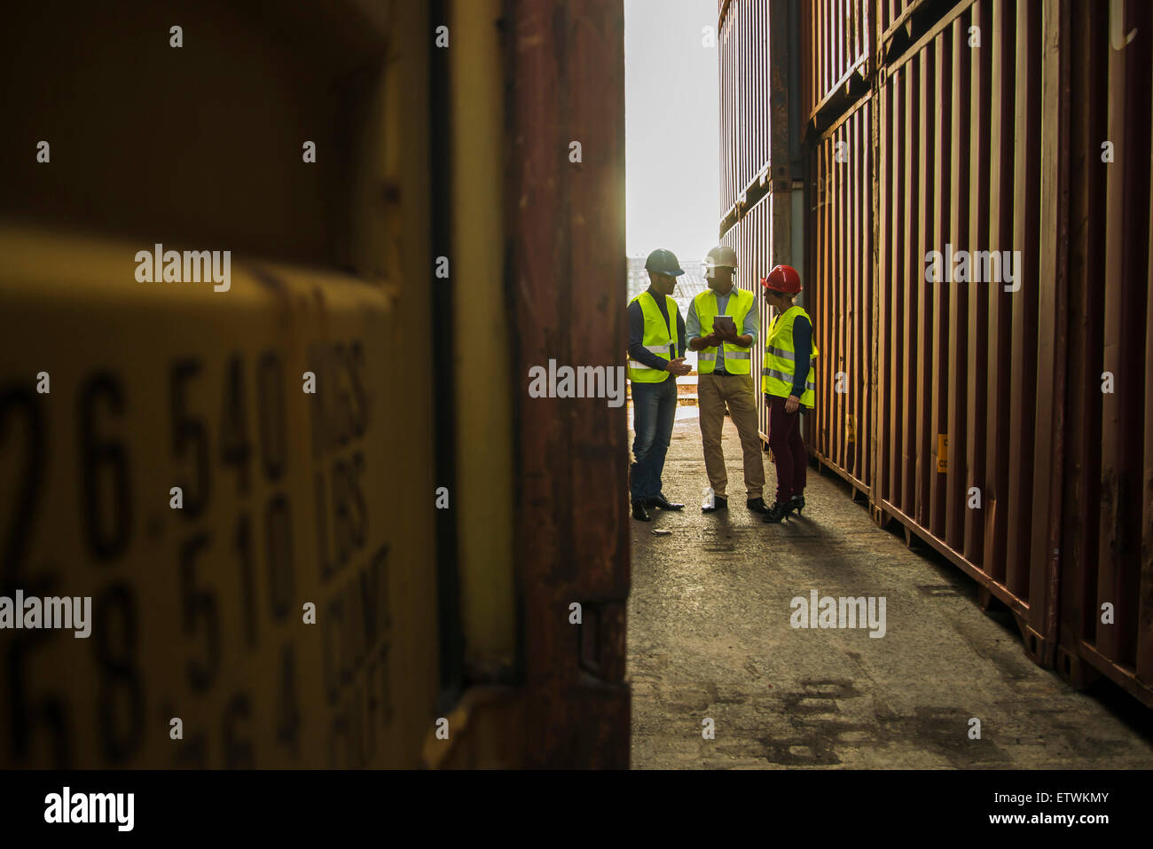 Woman and two men with safety helmets talking at container port - Stock Image