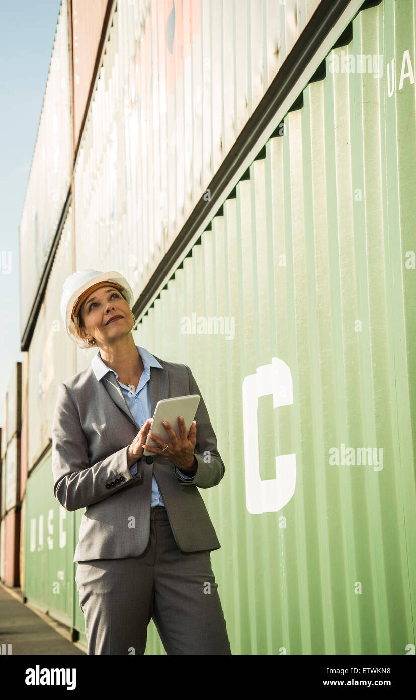 Businesswoman with digital tablet wearing safety helmet at container port - Stock Image