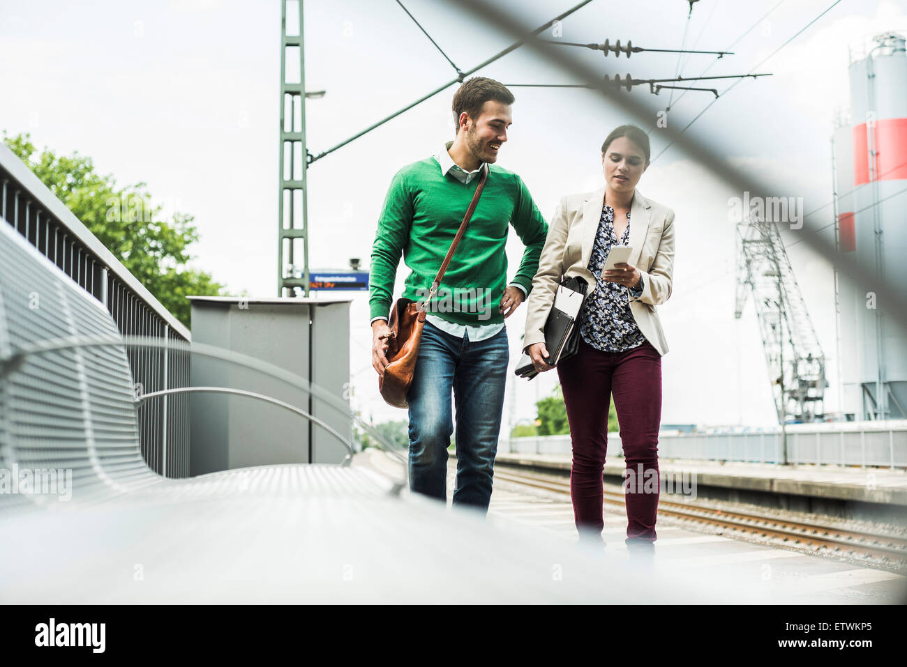 Young man and woman with cell phone on railway platform - Stock Image