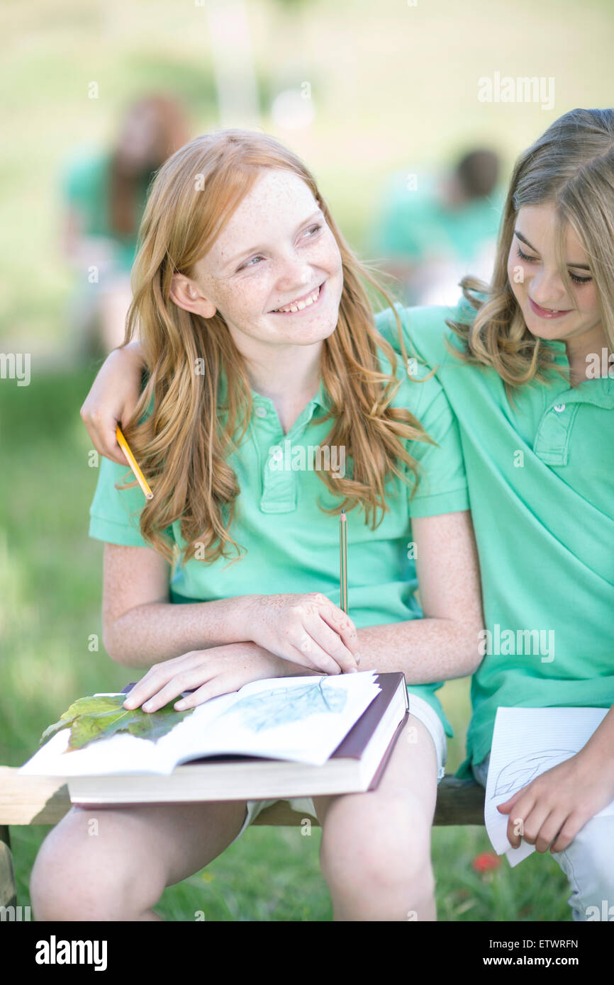 Portrait of girl with exercise book and leave in a park - Stock Image