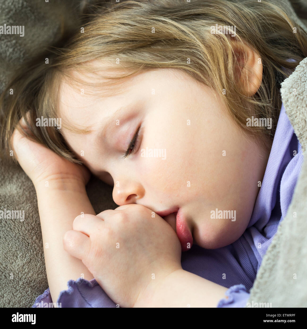 Sleeping little cute baby sucking thumb - Stock Image