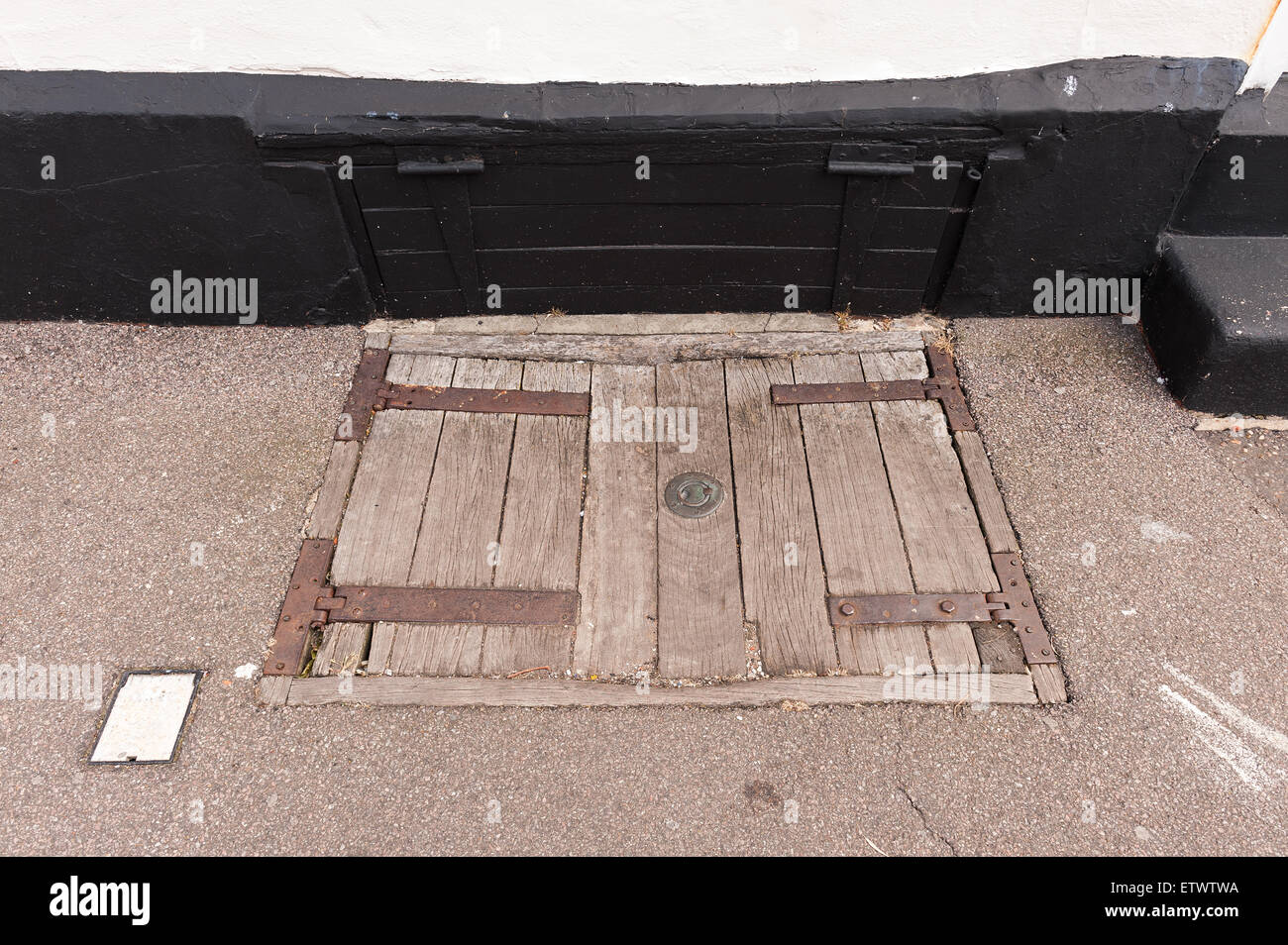 Old sun bleached weathered and worn oak street trapdoors in pavement for deliveries to a public house Stock Photo