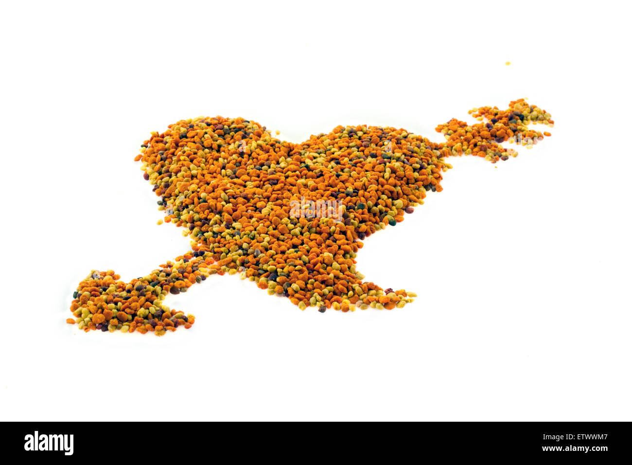 heart with arrow shaped dried honey bee pollen grains mix macro - Stock Image