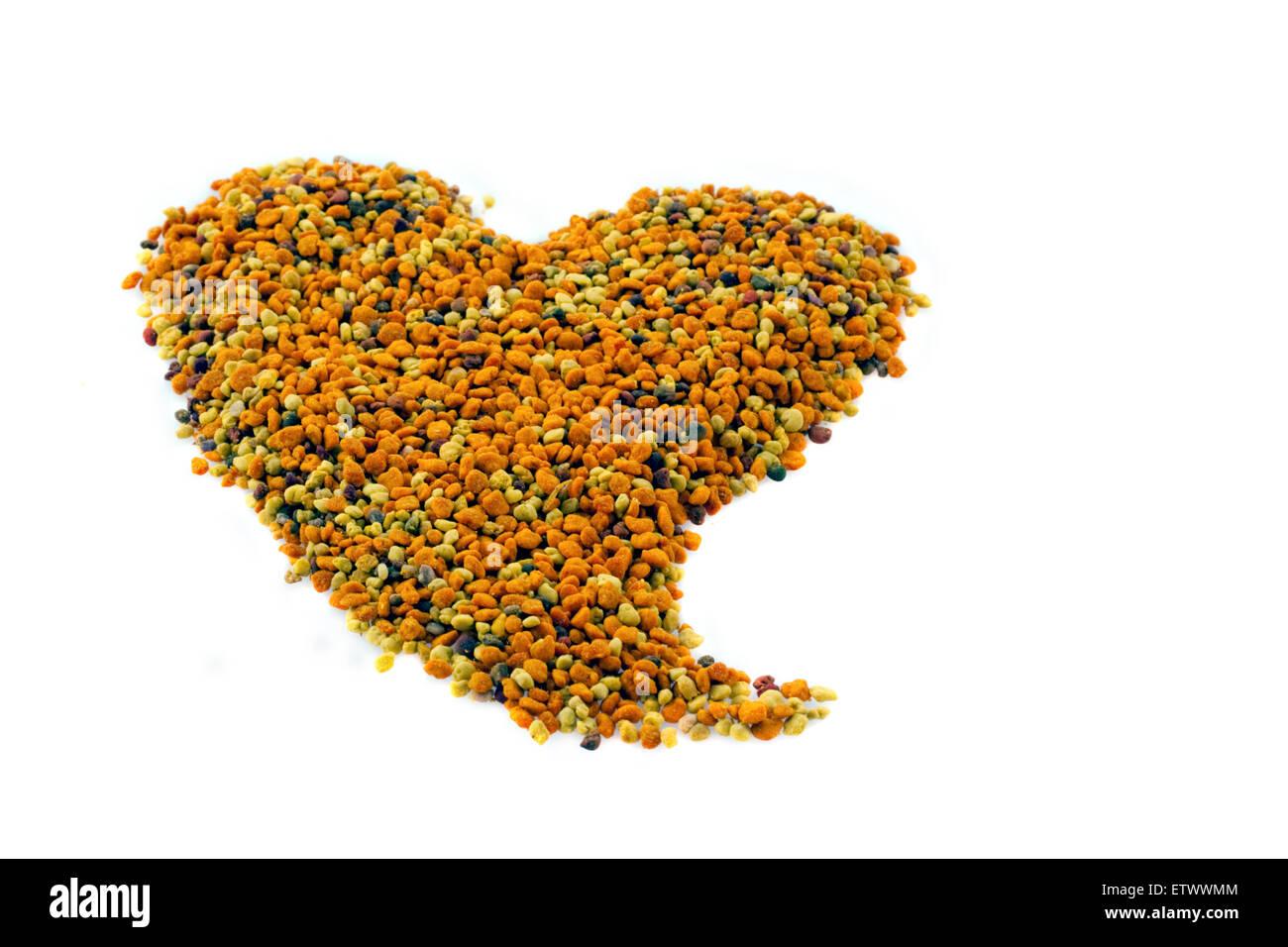 heart shaped raw dried apis honey bee pollen grains mix vitamins natural medicine macro - Stock Image