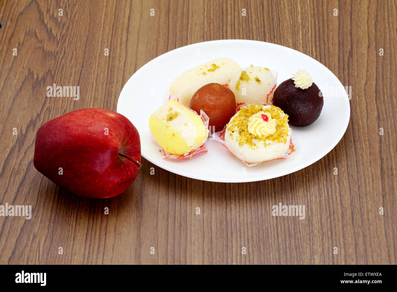 Indian sweets and apple on a wooden table - Stock Image