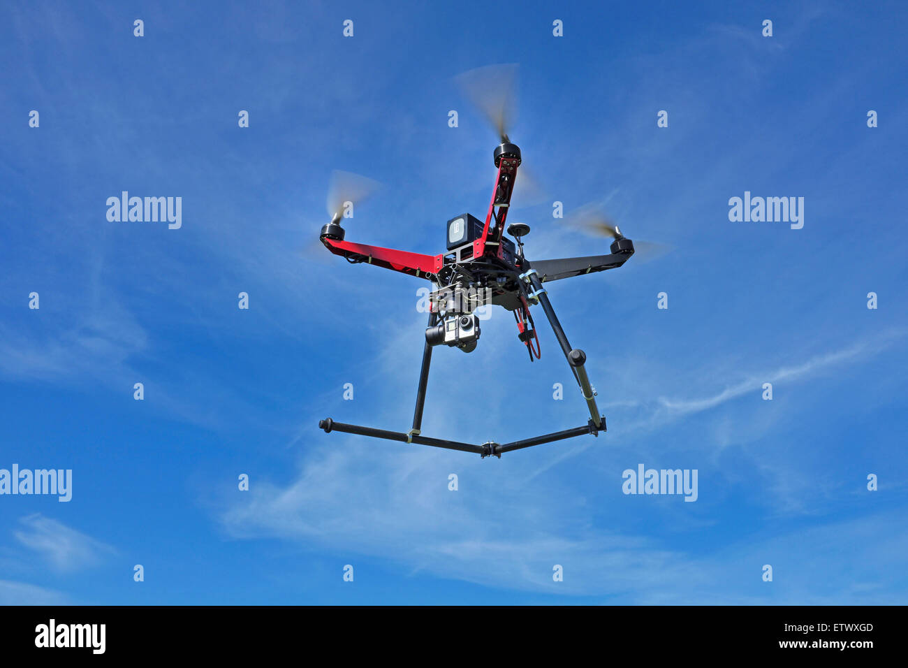 A quadcopter drone, equipped with a gopro camera, in flight. - Stock Image