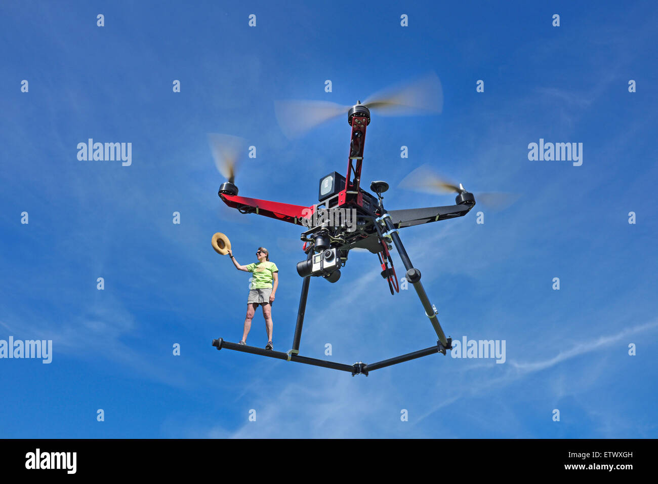 Same day delivery via a quadcopter drone, equipped with a gopro camera, in flight. - Stock Image