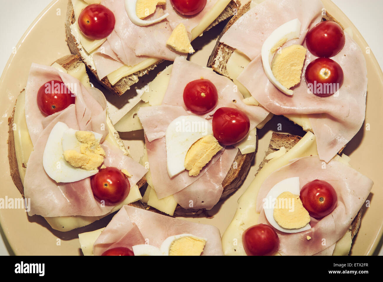 Tasty sandwiches with egg, cheese, ham and cherry tomatoes. Food and drink theme. Stock Photo