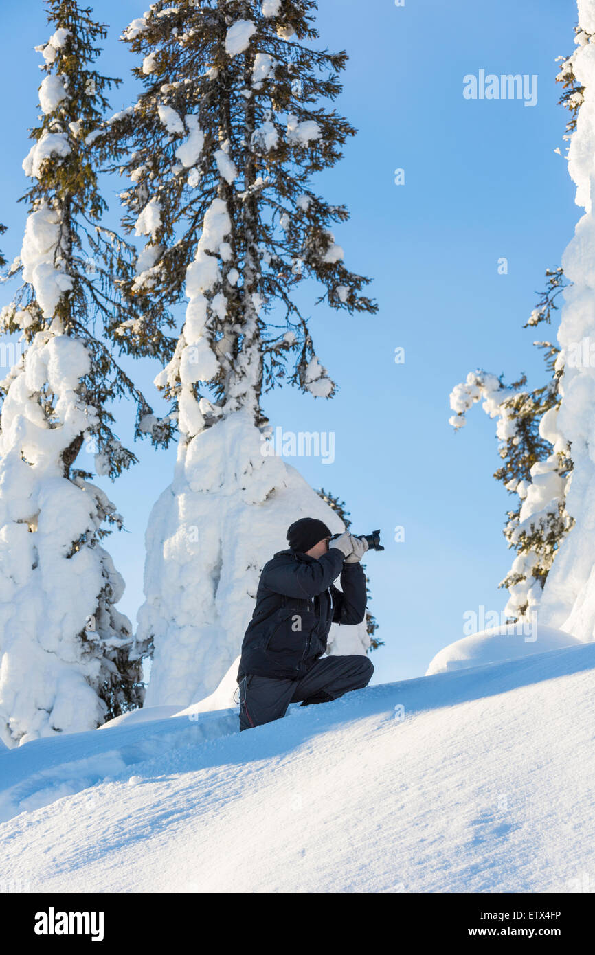 photographer taking picture of winter landscape - Stock Image