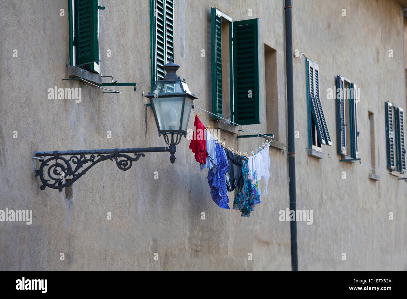 Laundry hanging outside window with an old street light beside it in the city of Volterra i Tuscany in Italy - Stock Image