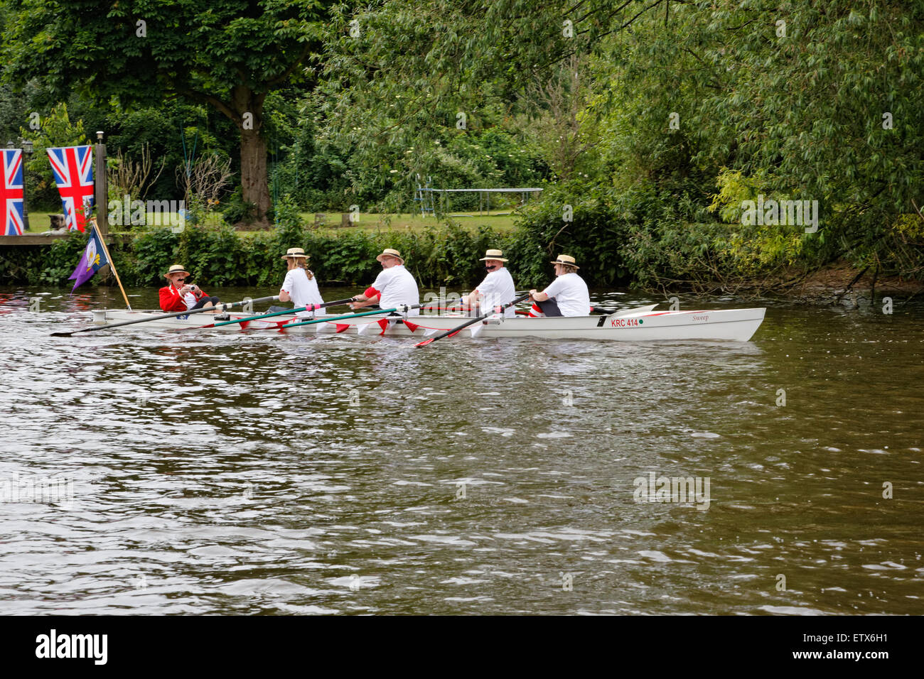 Coxed Four rowing on the River Thames at Runnymede in straw boaters and mustaches. - Stock Image