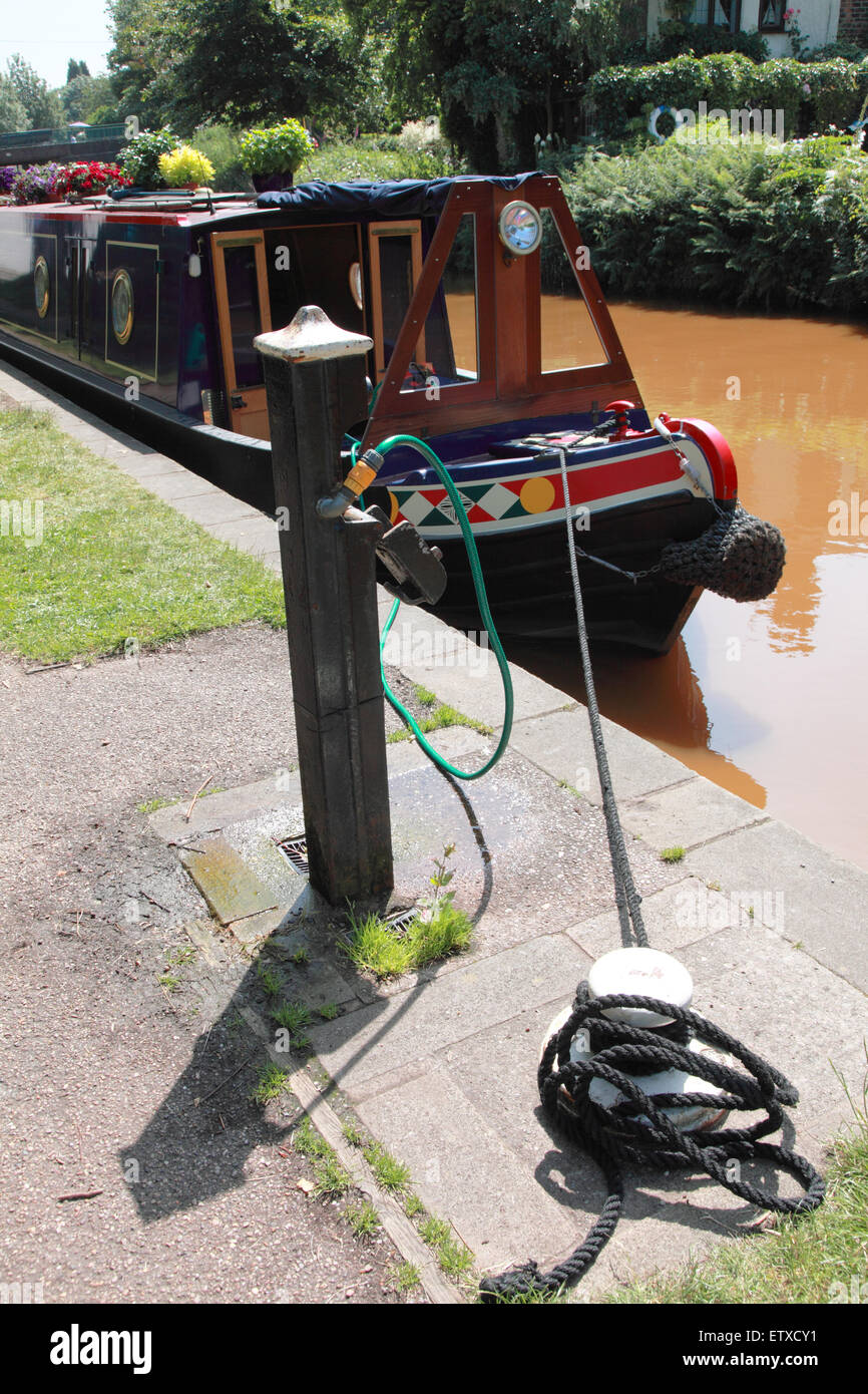A narrowboat tied up at a water point on the Trent and Mersey Canal with its water tank being refilled - Stock Image