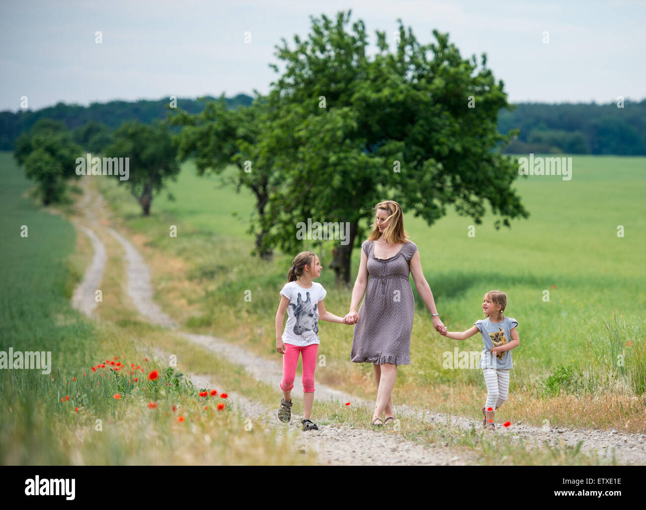 A mother and her two daughters take a walk along a field road during summery 30 degrees Celsius near Prötzel - Stock Image