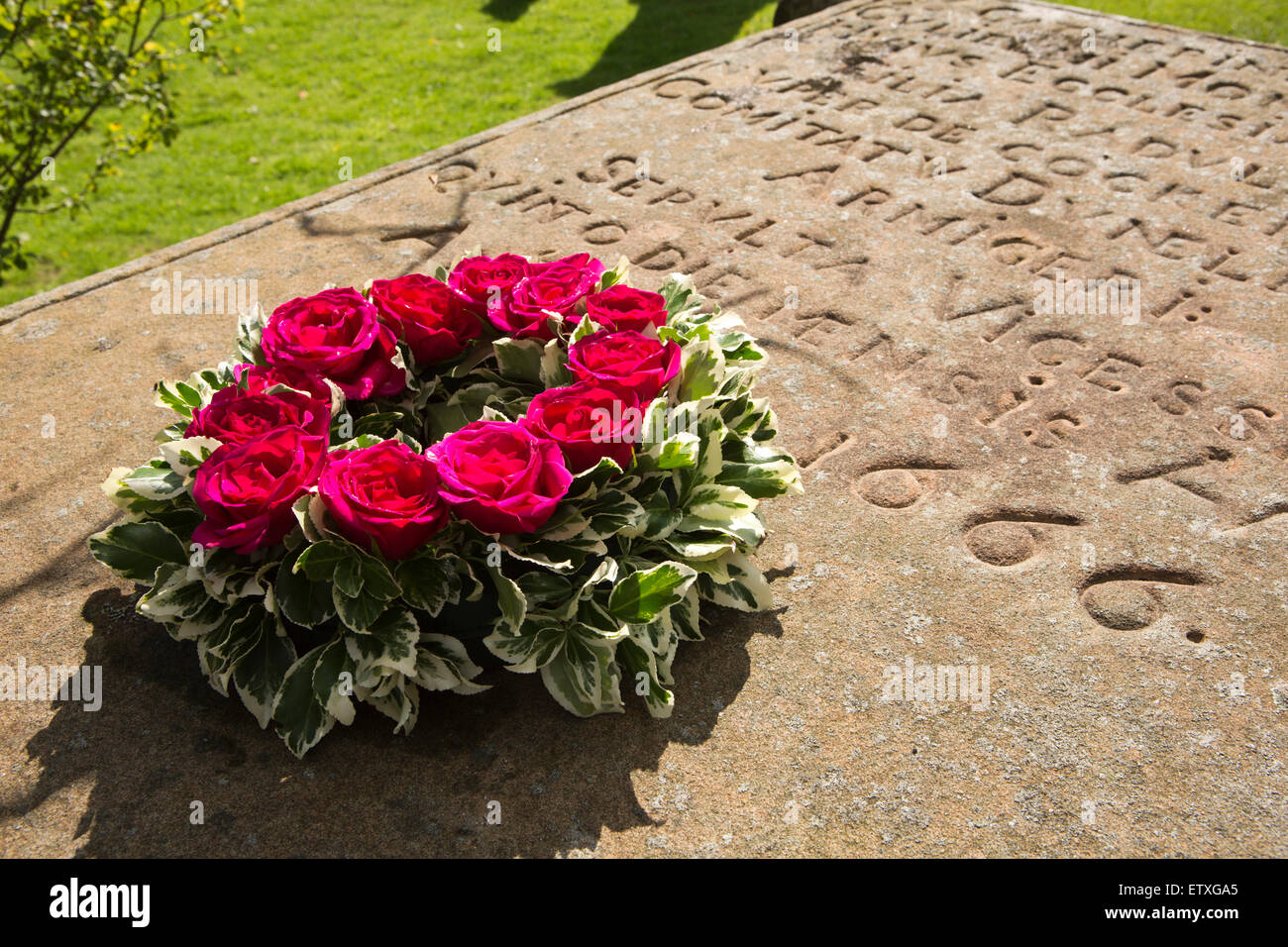 UK, England, Derbyshire, Eyam, roses wreath on Catherine Mompesson's grave, only plague victim in St Lawrence's - Stock Image