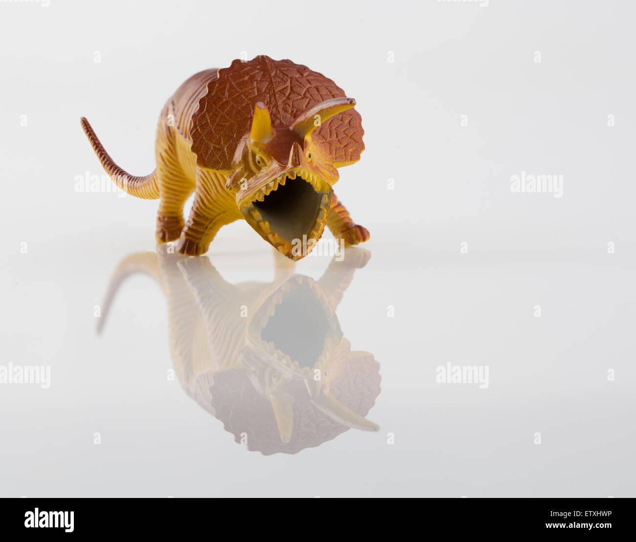Yellow angry dinosaur toy isolated on white - Stock Image