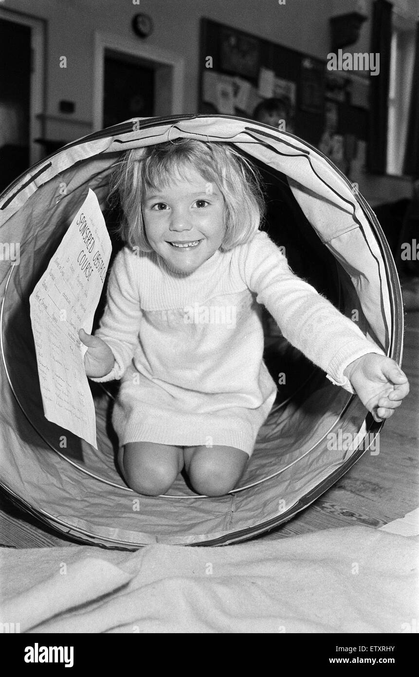 Tunnelling for sponsorship cash is four-year old Helen Copley who took part in an obstacle course at Lindley Playgroup - Stock Image