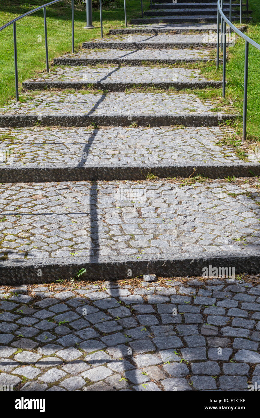 Road Paved with Brick-Stones with a Shadowy Leading Line - Stock Image